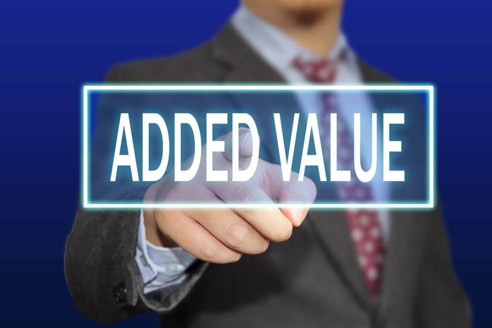 Business concept image of a businessman clicking Added Value button on virtual screen over blue background