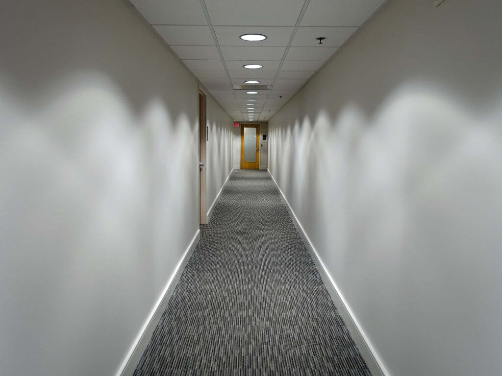 picture showing a renovated corridor with paint and new ceiling tiles.